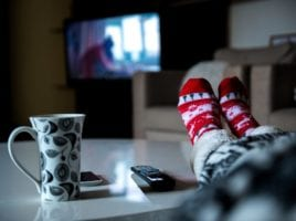 woman with warm socks on and a mug watching tv with heat on